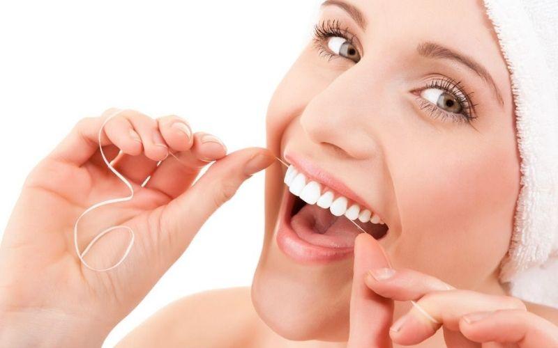 Sử dụng chỉ nha khoa để loại bỏ hoàn toàn thức ăn tồn tại trong khoang miệng